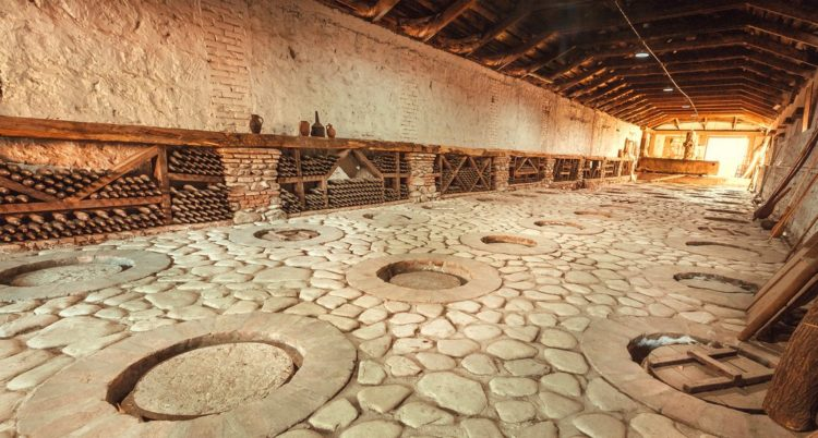 Huge stone cellar with aged dust wine bottles and qvevri, large earthenware vessels under ground. Rustic farmhouse interior with rural storage of winery