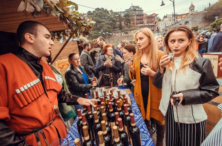 Tbilisi, Georgia - October 16, 2016: Women talking about wine with Georgian man during the Tbilisoba festival