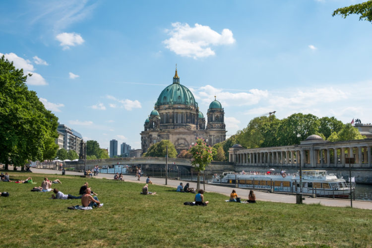 Berlin, Germany - may 23, 2017:People relaxing on meadow in Monbijoupark on a sunny day in Berlin with the Berlin cathedral and tourist boat in background.