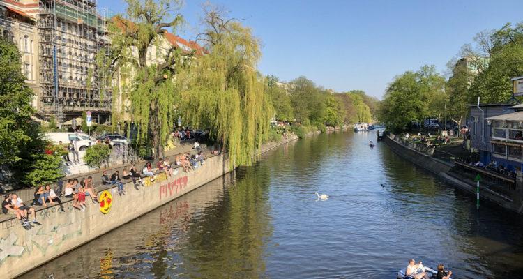 Berlin, Germany - april 2019: People enjoying sunny weather on the street, sitting at riverside in Berlin, Kreuzberg during spring